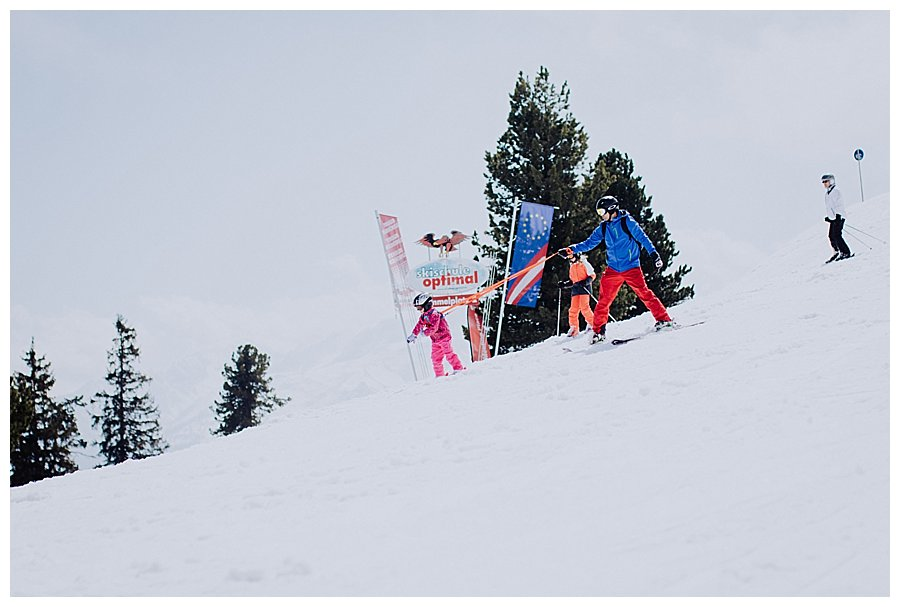 A child skiing down a ski slope on a leash