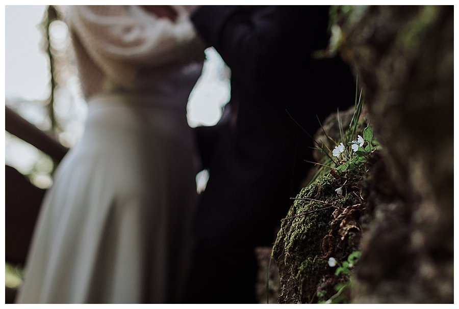 Close up of white flowers growing from the rocks with the bride and groom in the background