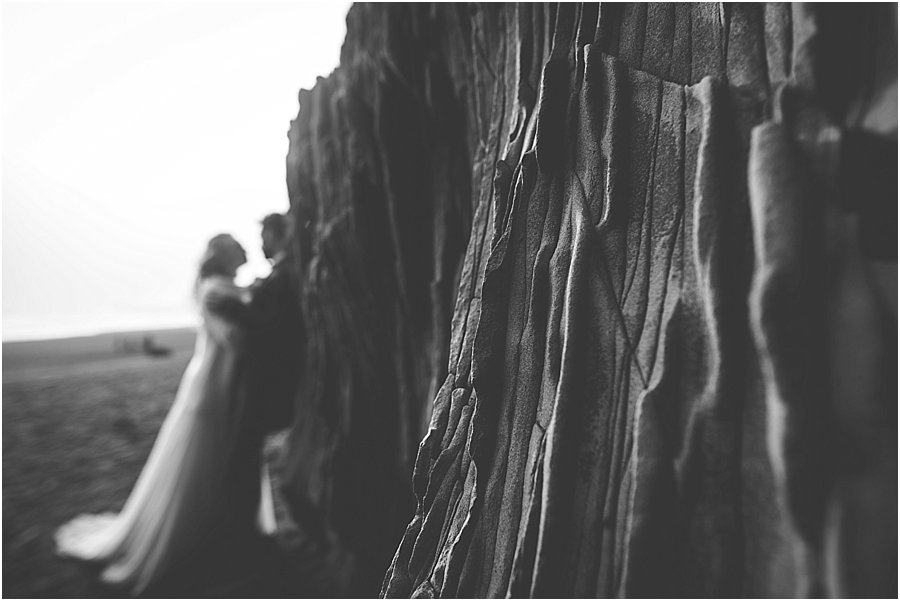 Blurry picture of bride and groom leaning against the rock wall
