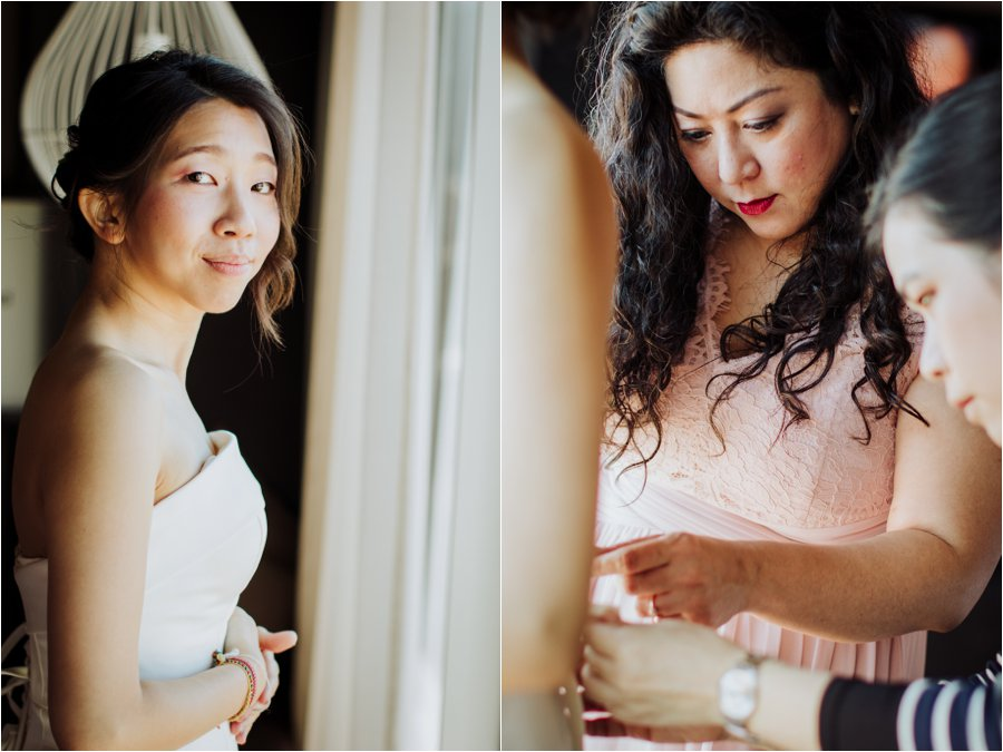 The bride Kelly getting ready as the bridesmaids lace up her wedding dress by Wild Connections Photography