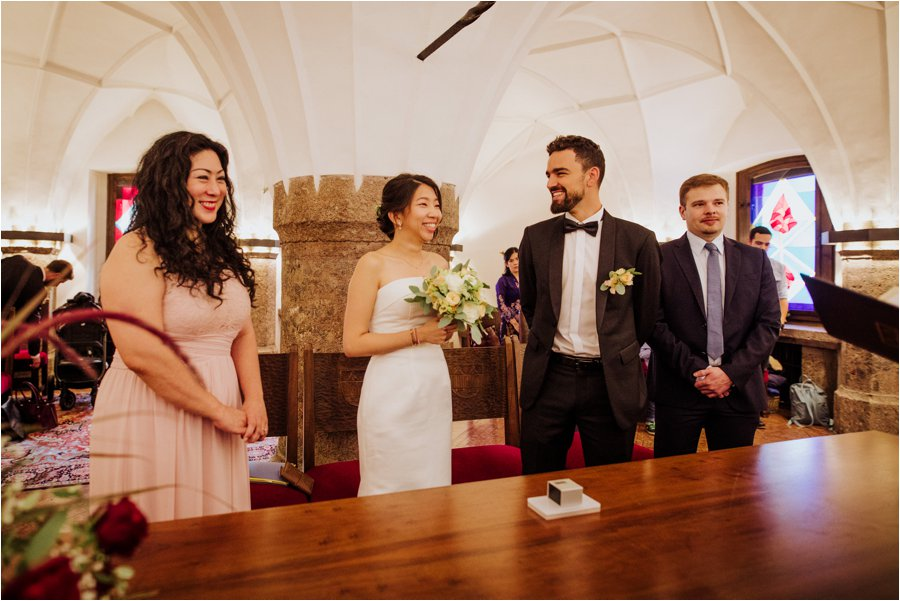 Kelly and Arik stand to say their wedding vows in the golden roof in Innsbruck for their civil wedding ceremony by Wild Connections Photography