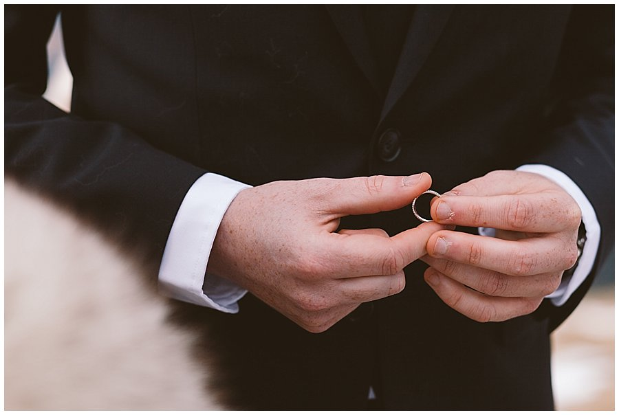 a close up picture of Lee holding Steph's wedding band