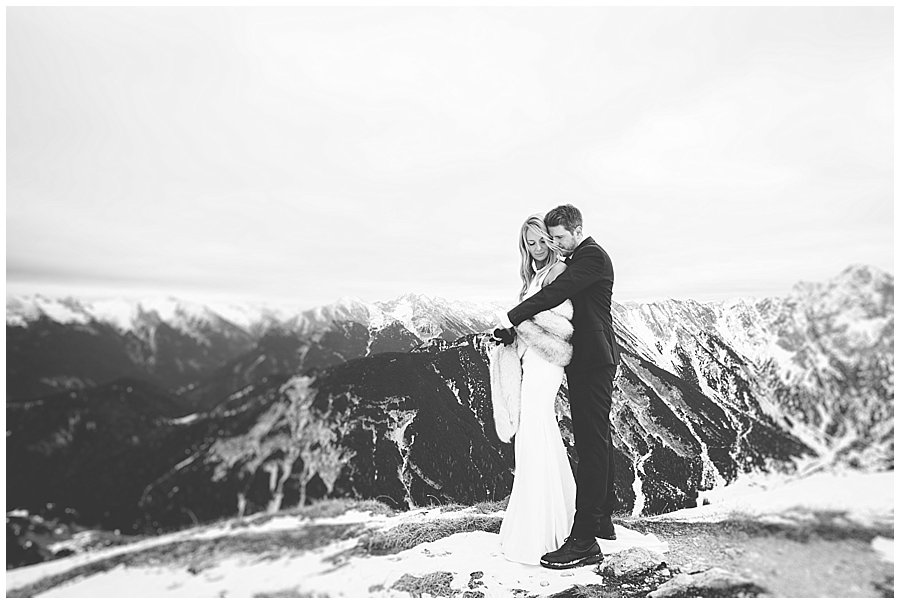 Steph and Lee embrace with a mountain panorama behind them