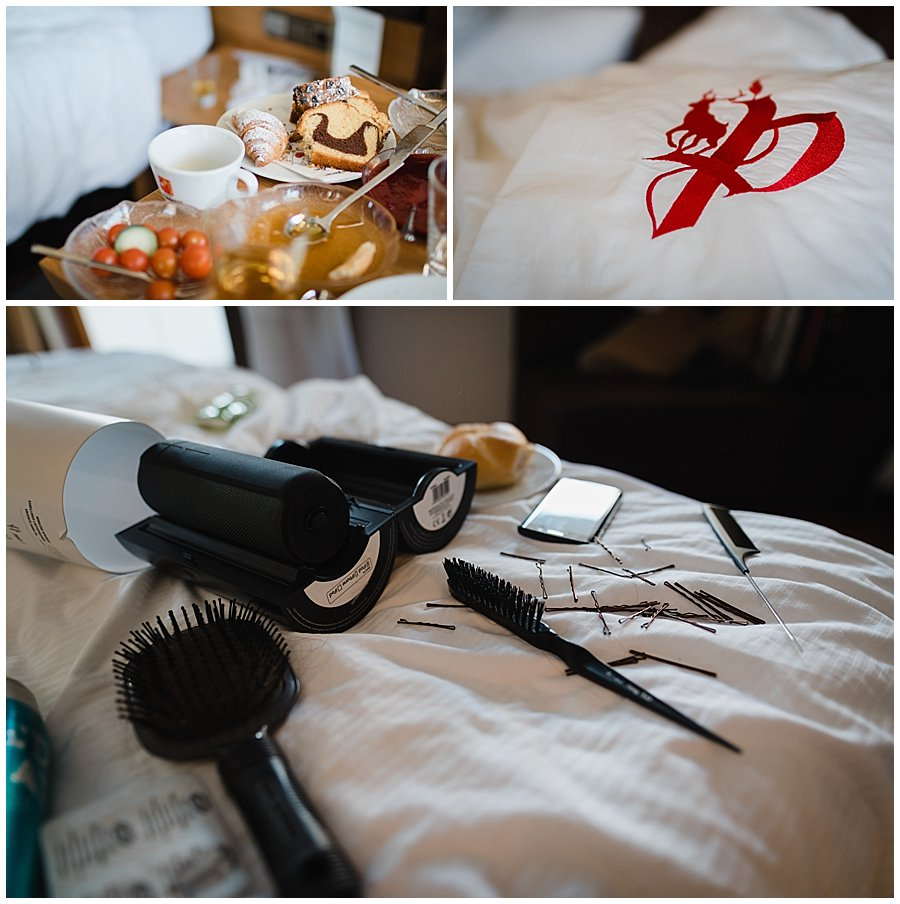 Image of a messy hotel room with breakfast on the table and hair accessories on the bed