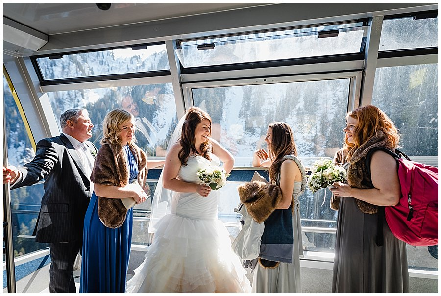 Bride and bridesmaids laugh as they ride up in the cable car