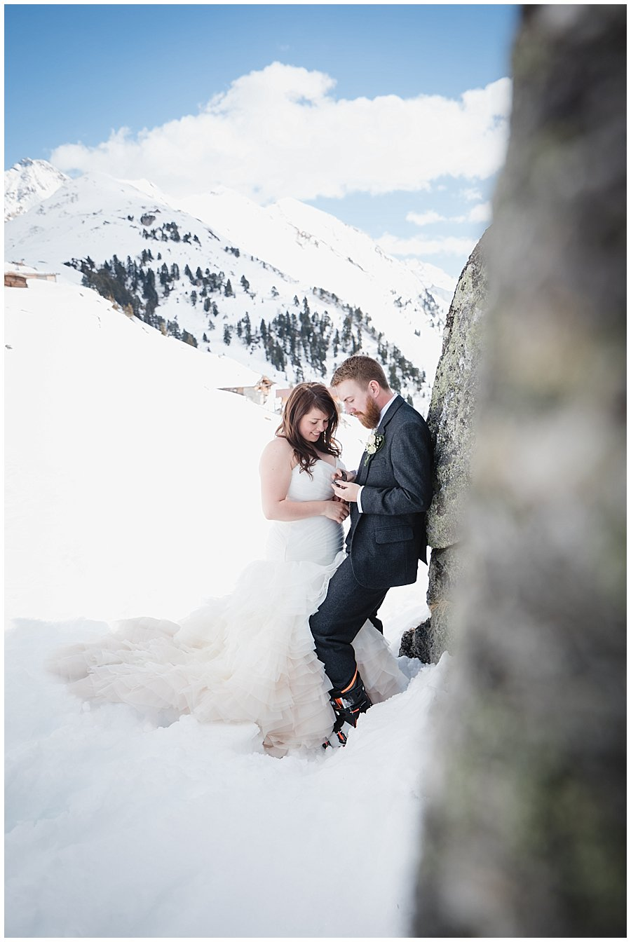 The bride and groom stand closely together in the snow as they look at something the groom is holding
