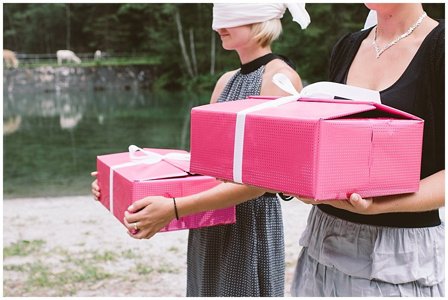 Women stand blindfolded holding pink boxes