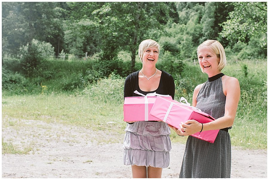 Women holding pink boxes and laughing