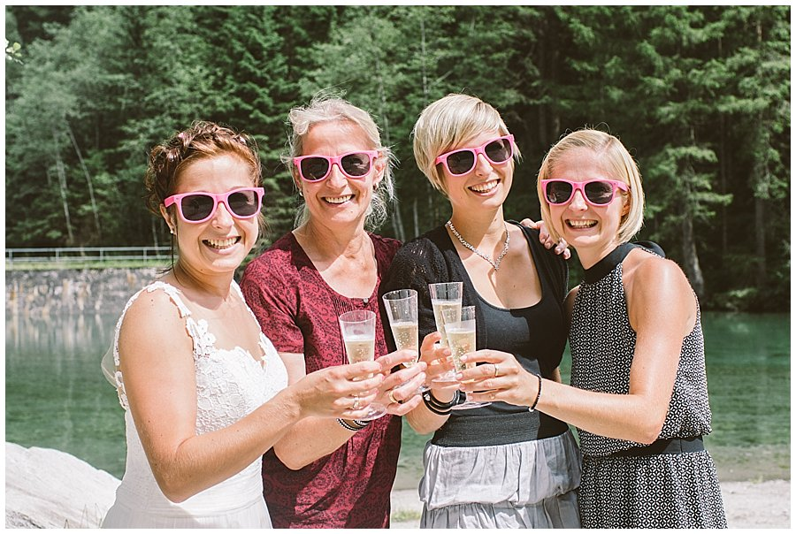 Girls toast with prosecco wearing pink sunglasses