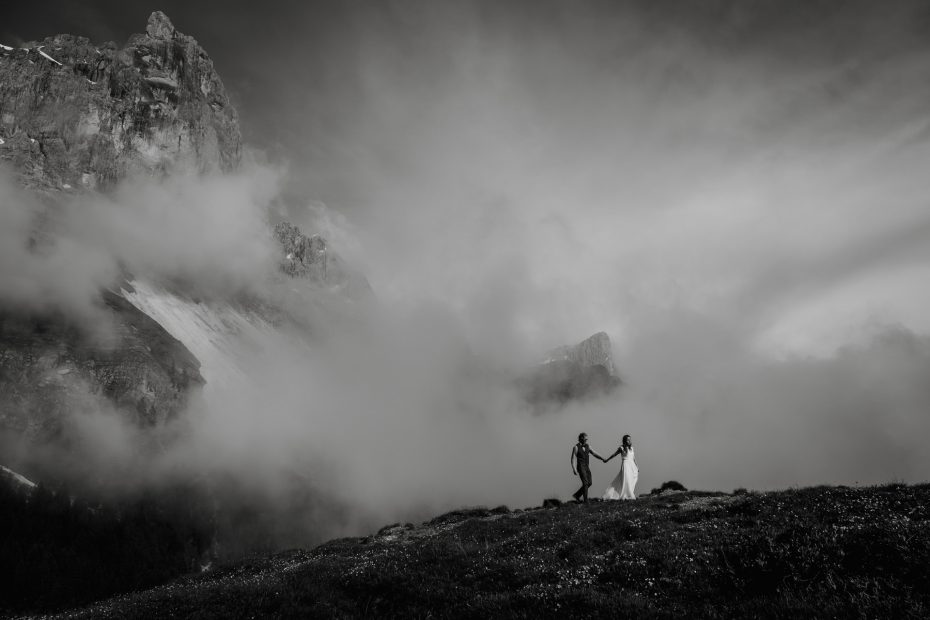 Couple hiking across a ridge in the Dolomites on their wedding day. Photo by Dolomites Elopement Photographer Wild Connections Photography